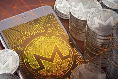 02_Monero-logo-in-a-smartphone-among-a-stack-of-coins.jpg